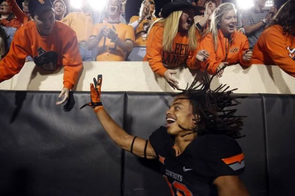 Photo - OSU cornerback Ramon Richards celebrates with fans after the Cowboys' 49-29 victory over TCU on Saturday. (Photo by Sarah Phipps)