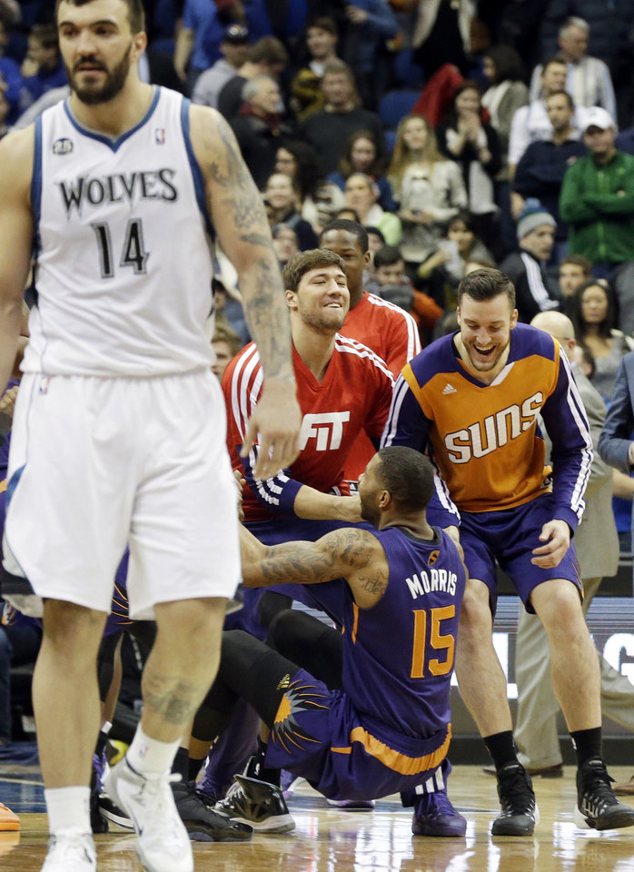 Photo - Minnesota Timberwolves' Nikola Pekovic, left, of Montenegro, leaves the court as Phoenix Suns players, including Marcus Morris (15) celebrate their come-from-behind 104-103 win in an NBA basketball game  Wednesday, Jan. 8, 2014, in Minneapolis. (AP Photo/Jim Mone)