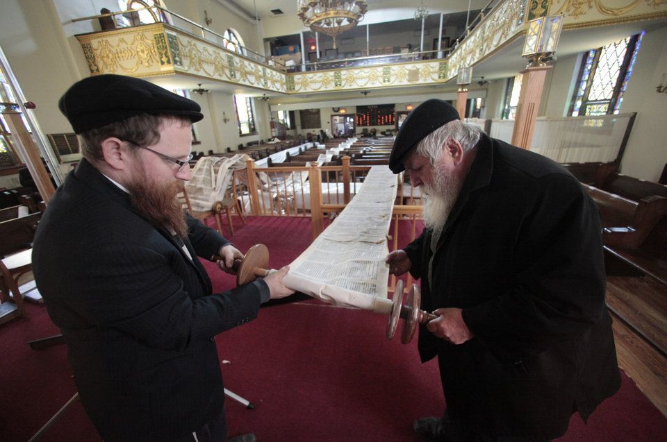 "Senior Rabbi Hershel Okonov, right, and his son Rabbi Dovid Okonov, roll a water-damaged Torah, one of six damaged in floods from Superstorm Sandy, stretched across pews, on Thursday, Nov. 1, 2012, at the Friends of Refugees of Eastern Europe (FREE) of Brighton Beach synagogue and community center in the Brooklyn borough of New York. ""I have never seen it like this,"" said Rabbi Dovid Okonov.  ""It broke my heart.""   Senior Rabbi Hershel Okonov added, ""if the Torahs can't be restored they have to be buried.""  (AP Photo/Bebeto Matthews) ORG XMIT: NYBM204"