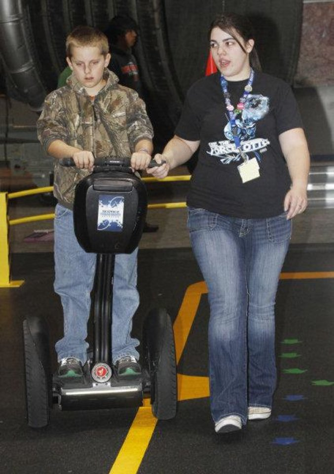 Zackrey Bond, a fifth-grader from Lexington, rides a Segway with help from Debra McClure at Science Museum Oklahoma. The museum celebrated Chemistry Day on Friday. Photo by Steve Gooch, The Oklahoman