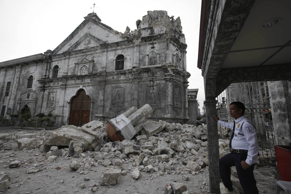 Photo - A private guard stands near the damaged Basilica of the Holy Child following a 7.2-magnitude earthquake that hit Cebu city in central Philippines and toppled the bell tower of the Philippines' oldest church Tuesday, Oct. 15, 2013. The tremor collapsed buildings, cracked roads and toppled the bell tower of the church Tuesday morning, causing multiple deaths across the central region and sending terrified residents into deadly stampedes. (AP Photo/Bullit Marquez)