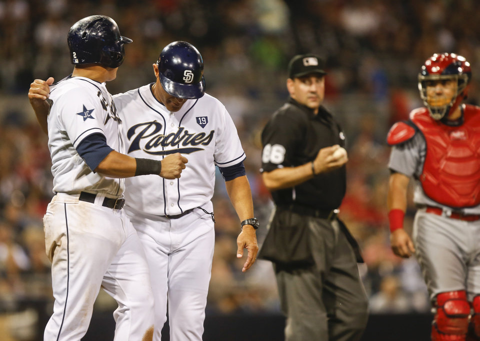 Photo - San Diego Padres first base coach Jose Valentin restrains Everth Cabrera as umpire David Rackley stands between the Padres and St. Louis Cardinals catcher Tony Cruz after the Cardinals hit Cabrera with a pitch during the Padres' eight run seventh inning in a baseball game Wednesday, July 30, 2014, in San Diego.  (AP Photo/Lenny Ignelzi)