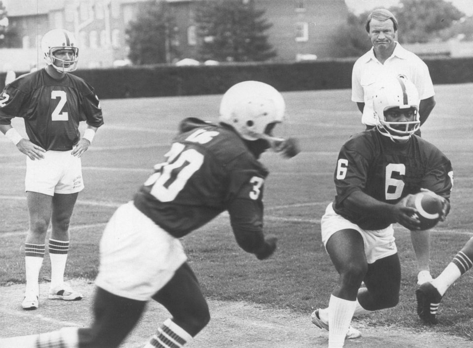 QB Thomas Lott, right, operates the wishbone with running back Kenny King during an OU practice in 1977. Coach Barry Switzer would call backup QB Dean Blevins, left, into games to throw a timely pass when the situation arose. Photo from the Oklahoman Archive