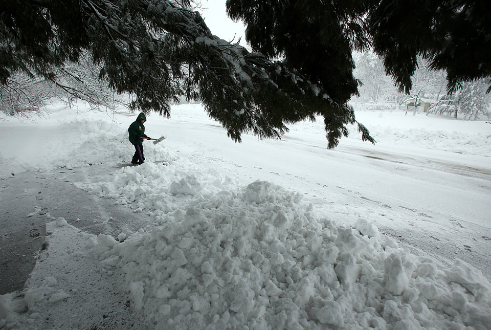 Photo - Chris Sauer shovels snow from her driveway during a winter snow storm in Oregon, Wis., Thursday, Dec. 20, 2012.  The first major snowstorm of the season began its slow eastward march across the Midwest early Thursday, creating treacherous driving conditions and threatening to disrupt some of the nation's busiest airports ahead of the holiday weekend.(AP Photo/Wisconsin State Journal,Amber Arnold.)