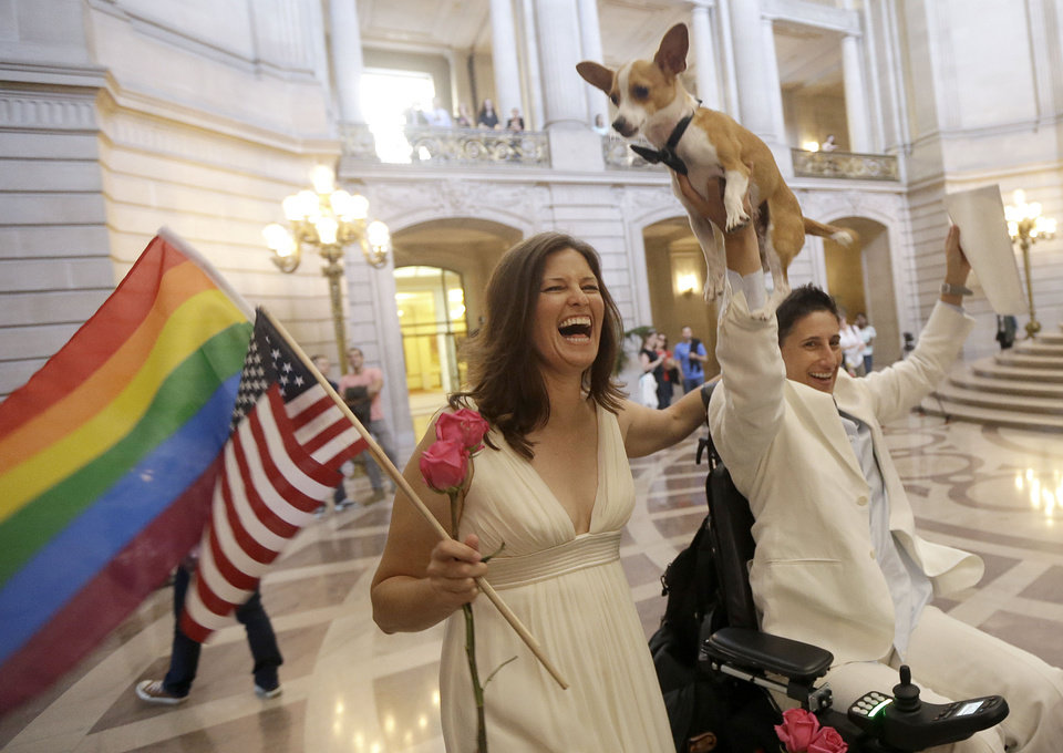 Photo - Jen Rainin, left, laughs as her wife Frances holds up their dog Punum after they were married at City Hall in San Francisco, Friday, June 28, 2013. A three-judge panel of the 9th U.S. Circuit Court of Appeals issued a brief order Friday afternoon dissolving,