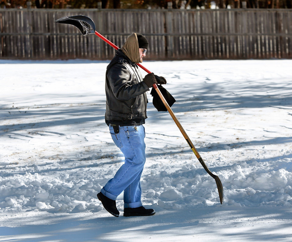 Photo - Erik White of Edmond totes a couple of shovels as he hikes about a half mile  through his neighborhood to Memorial Road Wednesday, Feb, 2, 2011,  to the street where a friend in a four-wheel drive truck met him  and gave him a ride to work in Oklahoma City.  Photo by Jim Beckel, The Oklahoman