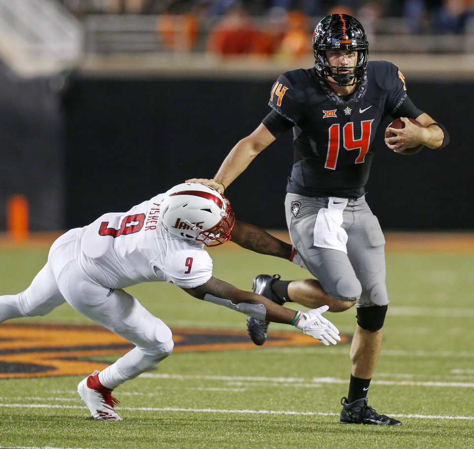Photo - Oklahoma State's Taylor Cornelius (14) escapes from South Alabama's Sterrling Fisher (9) on a carry in the third quarter during a college football game between Oklahoma State (OSU) and South Alabama at Boone Pickens Stadium in Stillwater, Okla., Saturday, Sept. 8, 2018. Photo by Nate Billings, The Oklahoman