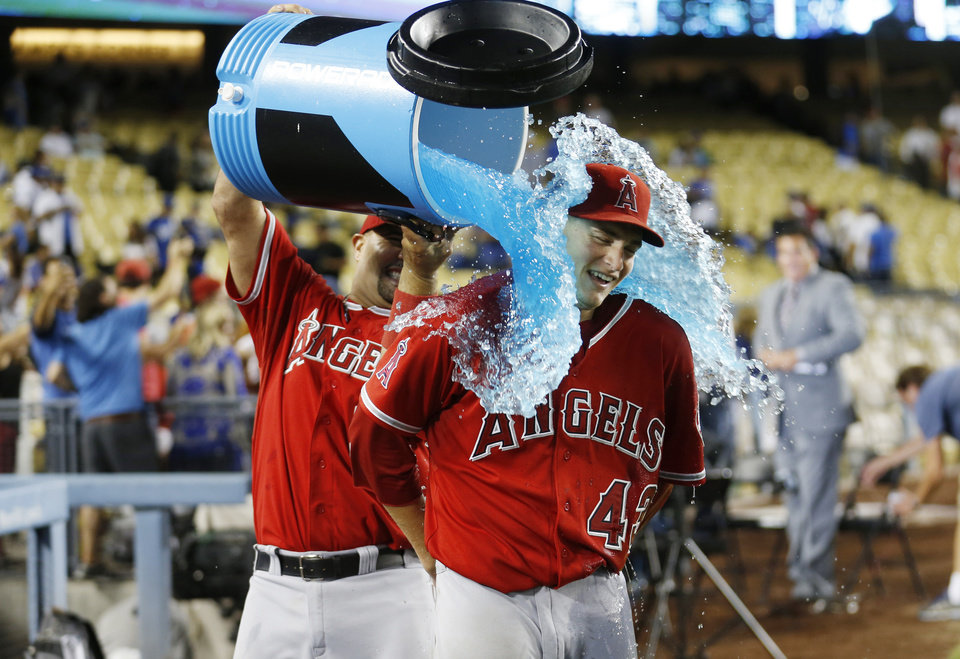 Photo - Los Angeles Angels' Albert Pujols, left, pours liquid over starting pitcher Garrett Richards in celebration after Richards pitched a complete game shutout win in a baseball game against the Los Angeles Dodgers, Monday, Aug. 4, 2014, in Los Angeles. The Angels won 5-0. (AP Photo/Danny Moloshok)