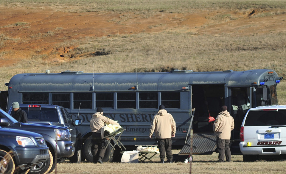 Law enforcement personnel load provisions into a bus during the third day of a hostage crisis involving a 5-year-old boy, in Midland City, Ala, Thursday, Jan 31, 2013. A standoff in rural Alabama went into a second full day Thursday as police surrounded an underground bunker where a retired truck driver was holding a 5-year-old hostage he grabbed off a school bus after shooting the driver dead. The bus driver, Charles Albert Poland Jr., 66, was hailed by locals as a hero who gave his life to protect the 21 students aboard the bus. (AP Photo/The Dothan Eagle, Jay Hare)