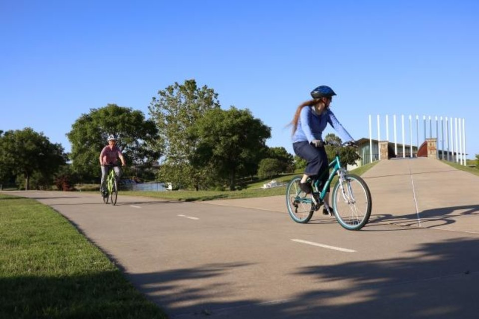 Photo -  People ride bikes along the Oklahoma River Trail near the Chesapeake Boathouse on Friday. [Doug Hoke/The Oklahoman]
