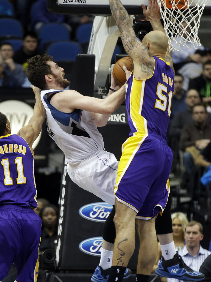 Photo - Minnesota Timberwolves' Kevin Love, center, is fouled by Los Angeles Lakers' Robert Sacre, right, during the second half of an NBA basketball game, Tuesday, Feb. 4, 2014, in Minneapolis. The Timberwolves won 109-99. Love, who led his team with 31 points and 17 rebounds, fell to the floor and was attended to but continued in the game. (AP Photo/Jim Mone)