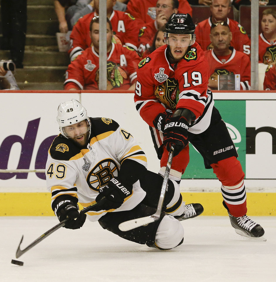 Photo - Boston Bruins center Rich Peverley (49) falls to the ice as he keeps the puck from Chicago Blackhawks center Jonathan Toews (19) in the second period during Game 2 of the NHL hockey Stanley Cup Finals, Saturday, June 15, 2013, in Chicago. (AP Photo/Nam Y. Huh)