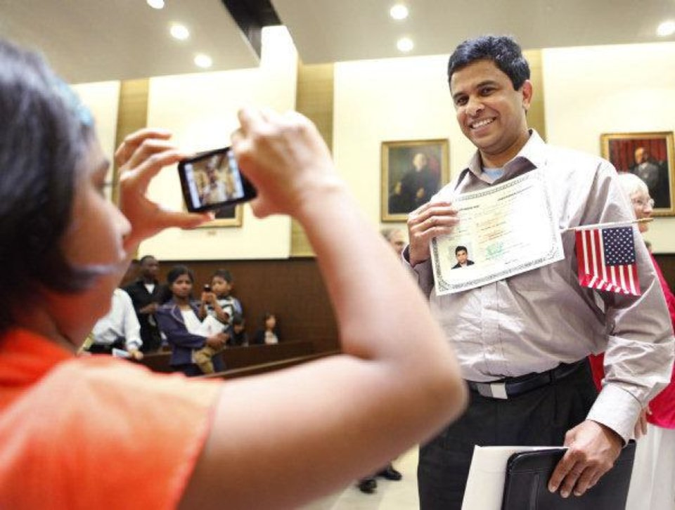 Photo - Eight-year-old Ann George takes a photo of her father, George Varghese, a new citizen from India, during a June 24 naturalizaiton ceremony at the federal courthouse in Oklahoma City.  PAUL HELLSTERN - THE OKLAHOMAN