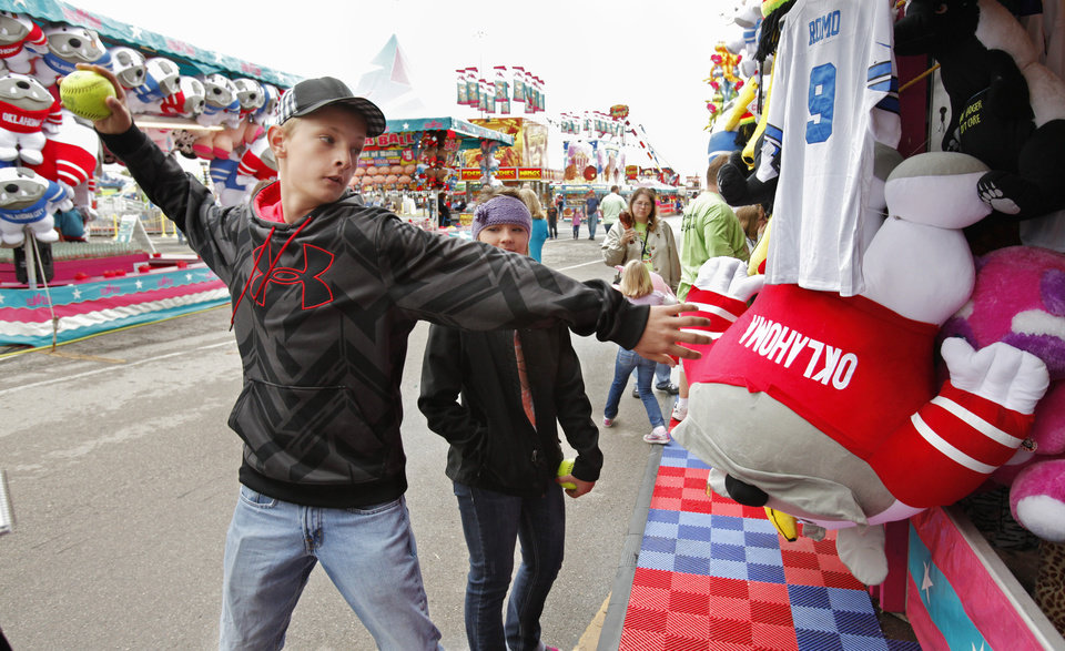 Drake Vaught, 15 from Willow, attempts to knock milk bottles off a platform on the midway of the 106th Oklahoma State Fair at State Fair Park on Saturday, Sept. 15, 2012, in Oklahoma City, Okla.  Photo by Steve Sisney, The Oklahoman