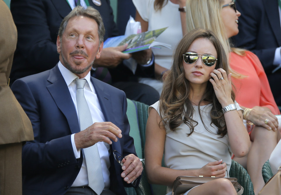 Photo - Larry Ellison, left, sits in the Royal Box on centre court prior to the men's singles semifinal  match between Novak Djokovic of Serbia and Grigor Dimitrov of Bulgaria at the All England Lawn Tennis Championships in Wimbledon, London, Friday July 4, 2014. (AP Photo/Pavel Golovkin)