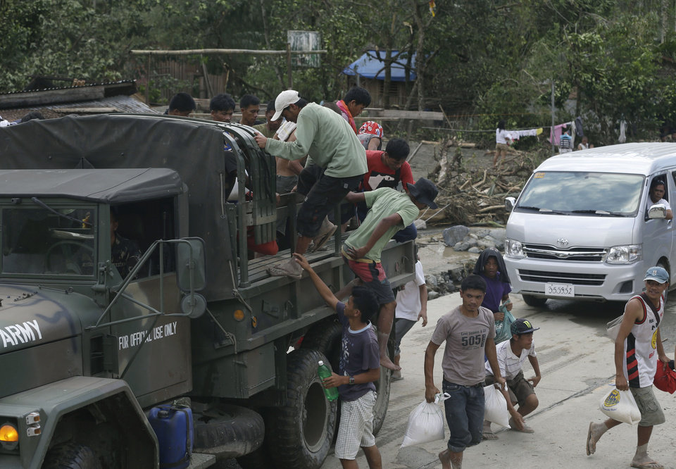 Residents jump off  a military truck after receiving food supplies in the flash flood-hit village of Andap, New Bataan township, Compostela Valley in southern Philippines Wednesday, Dec. 5, 2012. Typhoon Bopha, one of the strongest typhoons to hit the Philippines this year, barreled across the country's south on Tuesday, killing scores of people while triggering landslides, flooding and cutting off power in two entire provinces. (AP Photo/Bullit Marquez)