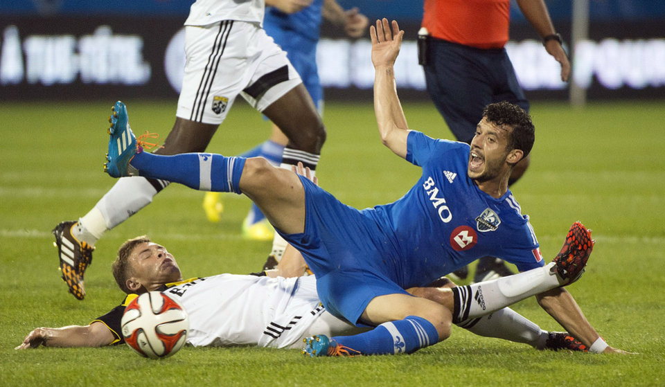 Photo - Montreal Impact's Felipe Martins, right, and Columbus Crew's Wil Trapp battle for the ball during first half MLS soccer action in Montreal, Saturday, Aug. 30, 2014. (AP Photo/The Canadian Press, Graham Hughes)