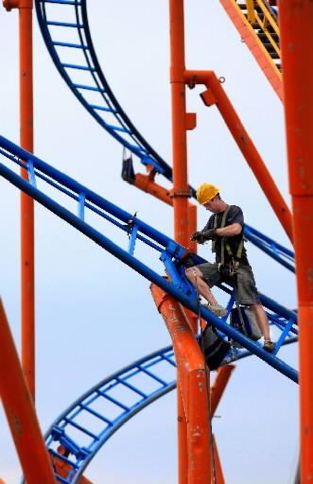 Photo - Raymond Niblack installs side bolts as he finishes assembling the RC 48 roller coaster before the opening of the Oklahoma State Fair. Niblack said it usually takes crews about five days to assemble this roller coaster.  JIM BECKEL - THE OKLAHOMAN