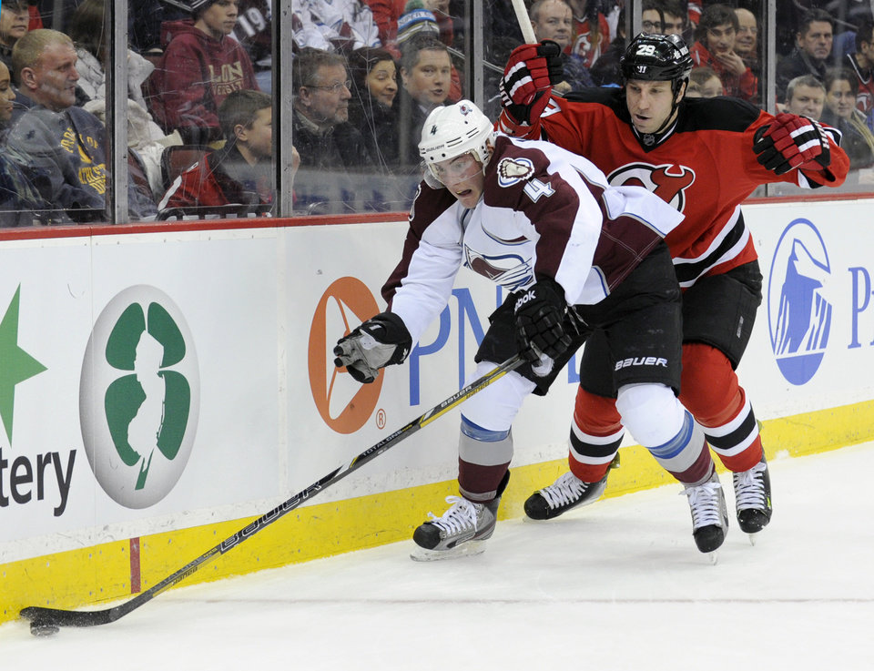 Colorado Avalanche's Tyson Barrie controls the puck as he is checked by New Jersey Devils' Ryan Clowe, right, during the second period of an NHL hockey game Monday, Feb. 3, 2014, in Newark, N.J. (AP Photo/Bill Kostroun)