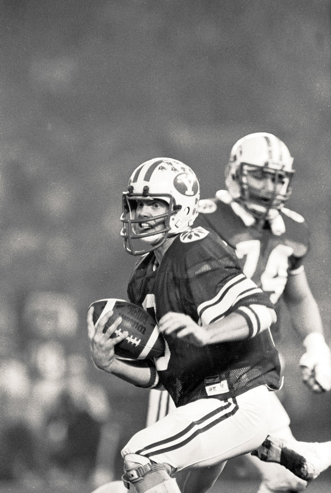 Photo - COLLEGE FOOTBALL: Brigham Young University quarterback Jim McMahon scrambles for yardage during his team's 38-36 victory over Washington State in the Holiday Bowl, Dec. 19, 1981, in San Diego.  McMahon, who threw for 342 yards and three touchdowns, was named the game's most valuable player.  (AP Photo) ORG XMIT: APHS