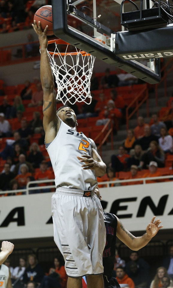 Photo - Oklahoma State wing Le'Bryan Nash (2) shoots in front of Delaware State forward Tyshawn Bell (5) in the second half of an NCAA college basketball game in Stillwater, Okla., Tuesday, Dec. 17, 2013. Oklahoma State won 75-43. (AP Photo/Sue Ogrocki)