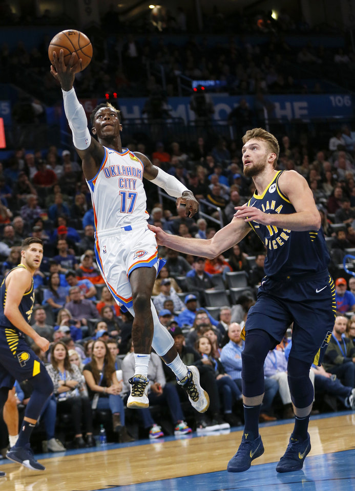 Photo - Oklahoma City's Dennis Schroder (17) takes the ball to the basket past Indiana's Domantas Sabonis (11) during an NBA basketball game between the Indiana Pacers and the Oklahoma City Thunder at Chesapeake Energy Arena in Oklahoma City, Wednesday, Dec. 4, 2019. [Nate Billings/The Oklahoman]