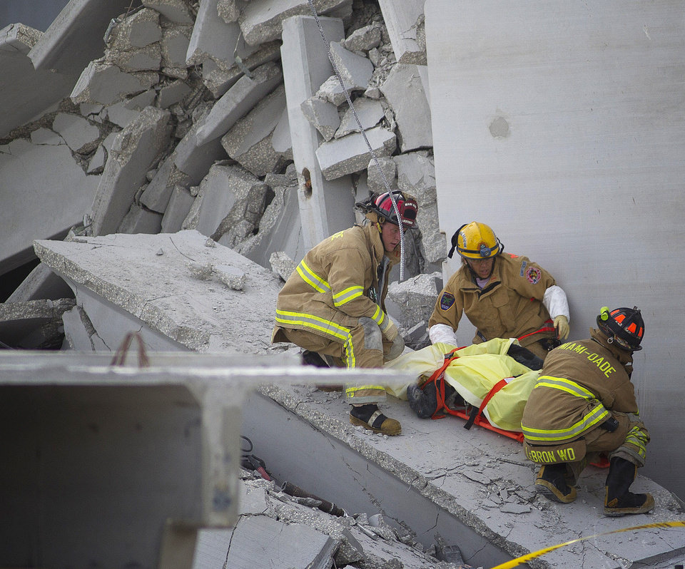 Photo -   Fire Rescue officials work to remove a victim from the collapsed parking garage at the Miami Dade College West campus in Doral, Fla. Tuesday, Oct. 10, 2012 . A section of a parking garage under construction at a community college collapsed killing one worker and trapping two others in the rubble, officials said. At least 10 other workers were hurt when the roof of the five-story concrete garage fell, creating a pancake-style collapse on the campus of Miami-Dade College, officials said. (AP Photo/J Pat Carter)