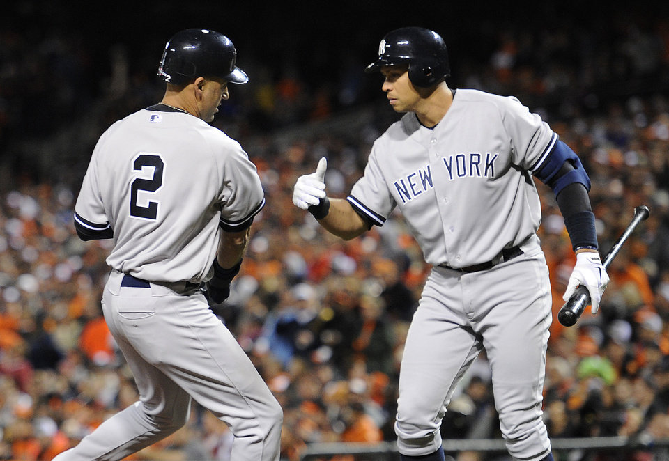 New York Yankees' Derek Jeter, left, high-fives teammate Alex Rodriguez after scoring a run on a double by Ichiro Suzuki, of Japan, in the first inning of Game 1 of the American League division baseball series against the Baltimore Orioles on Sunday, Oct. 7, 2012, in Baltimore. (AP Photo/Nick Wass)