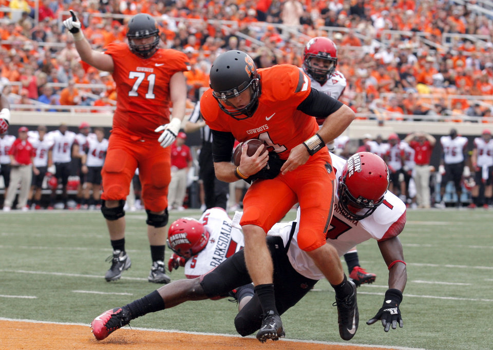 Oklahoma State\'s J.W. Walsh (4) rushes for a touchdown as Louisiana-Lafayette\'s Delvin Jones (7) tries to tackle him during a college football game between Oklahoma State University (OSU) and the University of Louisiana-Lafayette (ULL) at Boone Pickens Stadium in Stillwater, Okla., Saturday, Sept. 15, 2012. Photo by Sarah Phipps, The Oklahoman