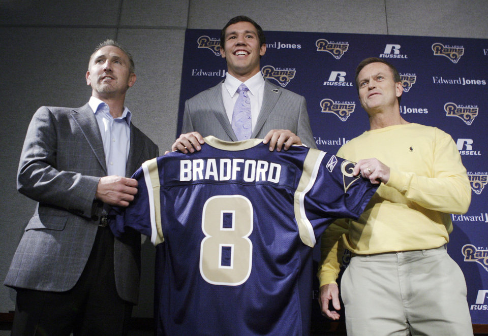 Photo - NFL FOOTBALL: St. Louis Rams quarterback Sam Bradford, center, holds up his new jersey alongside Rams head coach Steve Spagnuolo, left, and general manager Billy Devaney, right, before speaking to the media during an NFL news conference on Friday, April 23, 2010, in St. Louis. Bradford was selected as the No. 1 overall pick by the Rams in the first round. (AP Photo/Jeff Roberson) ORG XMIT: MOJR104