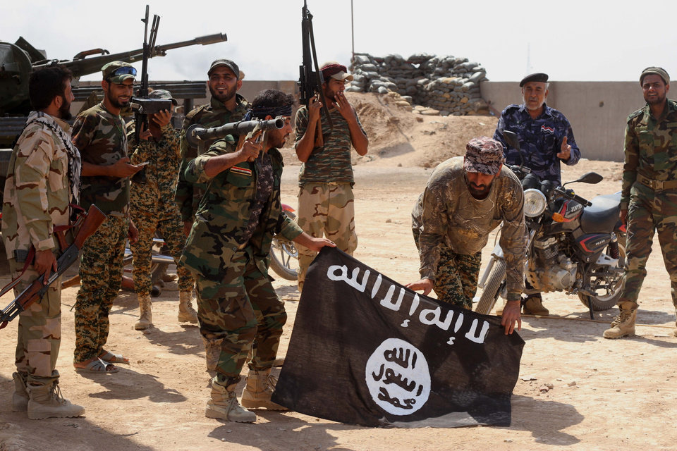 Photo - Iraqi security forces hold a flag of the Islamic State group they captured during an operation outside Amirli, some 105 miles (170 kilometers) north of Baghdad, Iraq, Monday, Sept. 1, 2014. Aid began flowing into the small northern Shiite town in Iraq on Monday, a day after security forces backed by Iran-allied Shiite militias and U.S. airstrikes broke a two-month siege by insurgents in a rare victory by government forces. (AP Photo)