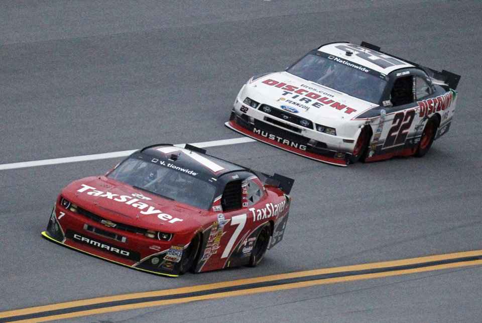 Photo - Regan Smith (7) leads Joey Logano (22) during the NASCAR Nationwide Series auto race at Talladega Superspeedway in Talladega, Ala., Saturday, May 4, 2013. Smith won the race. (AP Photo/Butch Dill)