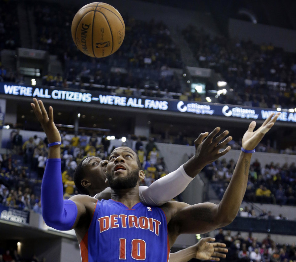 Photo - Indiana Pacers center Ian Mahinmi, back, comes from behind to knock the ball away from Detroit Pistons forward Greg Monroe in the first half of an NBA basketball game in Indianapolis, Monday, Dec. 16, 2013.  (AP Photo/Michael Conroy)