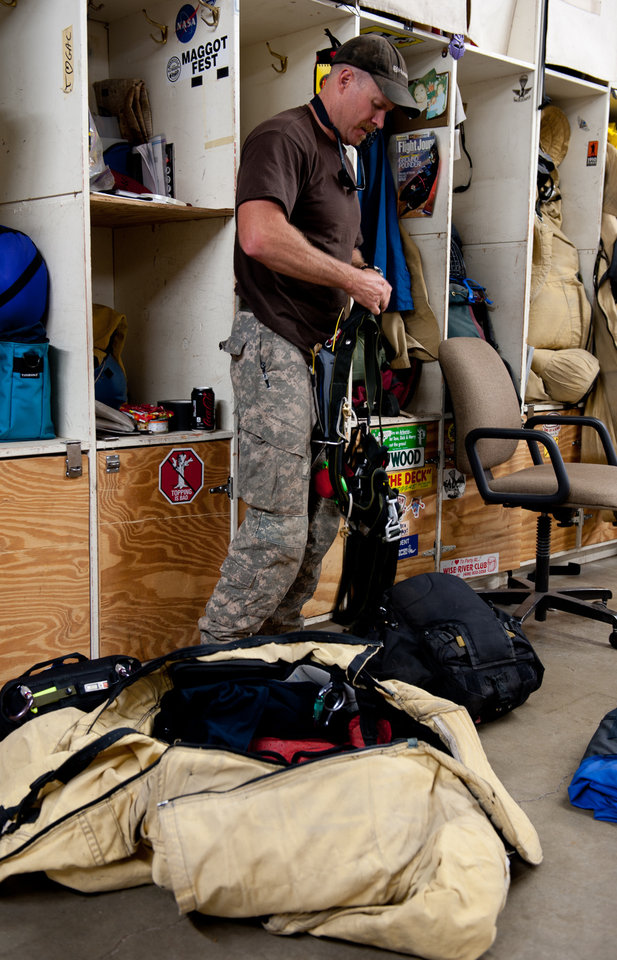Photo - This undated photo provided by the Missoula Smokejumper Base in Missoula, Mont., shows a smokejumper preparing gear and supplies.  Throughout the summer, public tours are offered daily at Missoula's  Aerial Fire Depot and Smokejumper Center, giving a look at the preparation and skill required of the smokejumpers who are trained to parachute in to attack fires in remote, rugged places. (AP Photo/Missoula Smokejumper Base, Donnie Sexton)