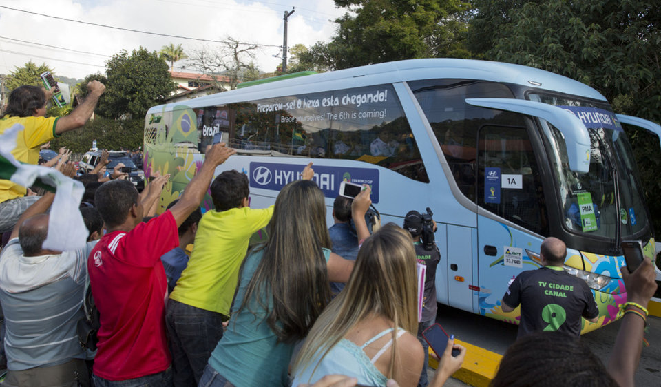 Photo - The bus carrying the Brazilian team is surrounded by fans outside the Granja Comary training center in Teresopolis Brazil, Sunday, June 15, 2014. Brazil plays in group A of the 2014 soccer World Cup. (AP Photo/Andre Penner)