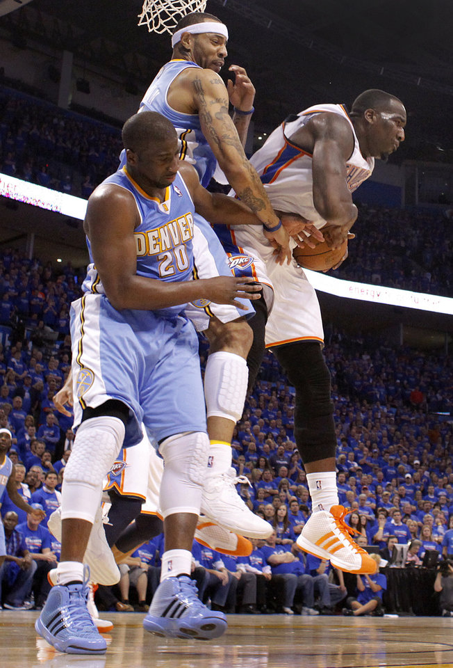 Photo - Oklahoma City's Kendrick Perkins (5) pulls in a rebound over Denver's Raymond Felton (20) and Denver's Kenyon Martin (4) during the first round NBA playoff game between the Oklahoma City Thunder and the Denver Nuggets on Sunday, April 17, 2011, in Oklahoma City, Okla. Photo by Chris Landsberger, The Oklahoman