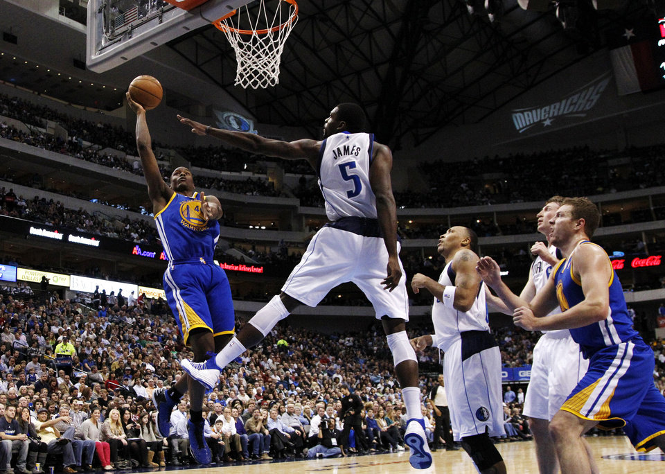 Golden State Warriors small forward Harrison Barnes (40) shoots as Dallas Mavericks center Bernard James (5) defends in the first half of an NBA basketball game, Monday, Nov. 19, 2012, in Dallas. Mavericks' Shawn Marion, third from right, Troy Murphy, second from right, and Warriors' David Lee watch on the play. (AP Photo/Tony Gutierrez)