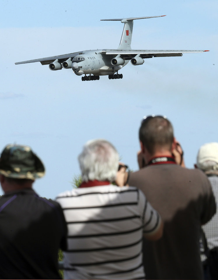 Photo - Spectators take photos of a Chinese  Ilyushin IL-76 aircraft as it comes in for a landing at Perth International Airport after returning from the ongoing search operations for missing Malaysia Airlines Flight 370 in Perth,  Australia, Thursday, April 10, 2014. With hopes high that search crews are zeroing in on the missing Malaysian jetliner's crash site, ships and planes hunting for the aircraft intensified their efforts Thursday after equipment picked up sounds consistent with a plane's black box in the deep waters of the Indian Ocean.  (AP Photo/Rob Griffith)