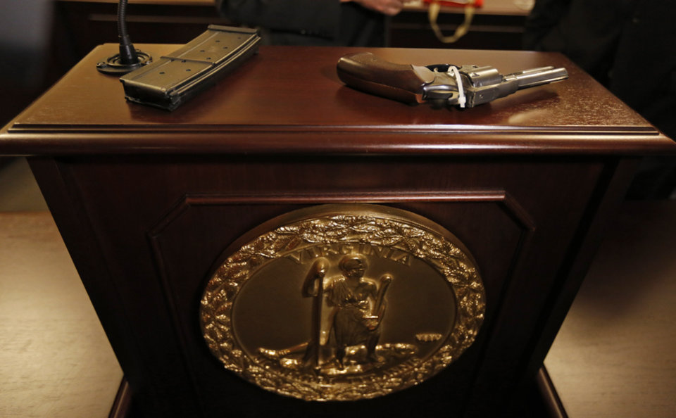 Photo - A pistol purchased from a northern Virginia gun show without a background check as well as a high capacity assault style rifle magazine are on display on the podium after a news conference on gun control legislation at the Capitol in  Tuesday, Jan. 15, 2013 in Richmond, Va.  (AP Photo/Steve Helber)