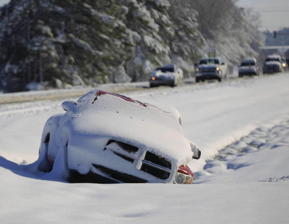 Photo - A vehicle abandoned by its driver lays buried in snow along the median of Mauamelle Blvd. in Little Rock, Ark. Wednesday morning, Dec. 26, 2012.  A historic Christmas night winter storm dropped upwards of a foot of snow on parts of Arkansas, shutting down workplaces, downing trees and power lines and turning travel treacherous. (AP Photo/The Arkansas Democrat-Gazette, Benjamin Krain)  ARKANSAS TIMES OUT; ARKANSAS BUSINESS OUT