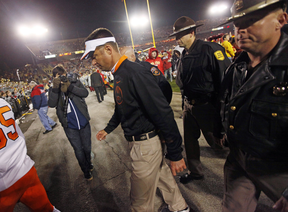 Photo - OSU head coach Mike Gundy leaves the field after a college football game between the Oklahoma State University Cowboys (OSU) and the Iowa State University Cyclones (ISU) at Jack Trice Stadium in Ames, Iowa, Friday, Nov. 18, 2011. Iowa State won, 37-31, in double overtime. Photo by Nate Billings, The Oklahoman