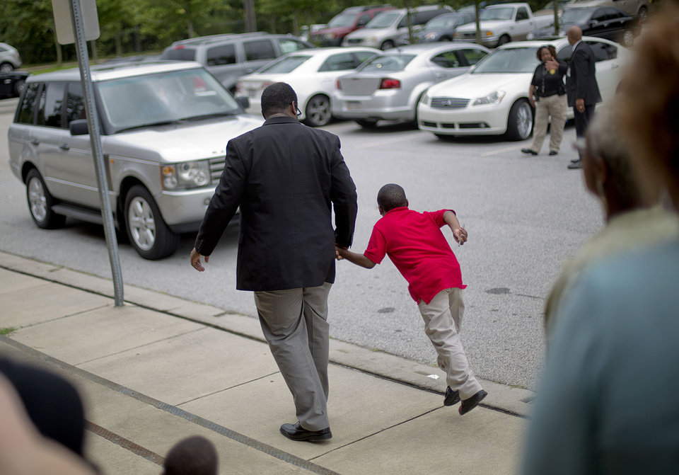 Photo - Ronald E. McNair Discovery Learning Academy teacher Brandon Graham walks a student to a car as he is picked up by a loved one at the end of their first day of classes at McNair High School Wednesday, Aug. 21, 2013 after a man with an assault rifle and other weapons entered the academy Tuesday and shot at police from inside, in Decatur, Ga. (AP Photo/David Goldman)