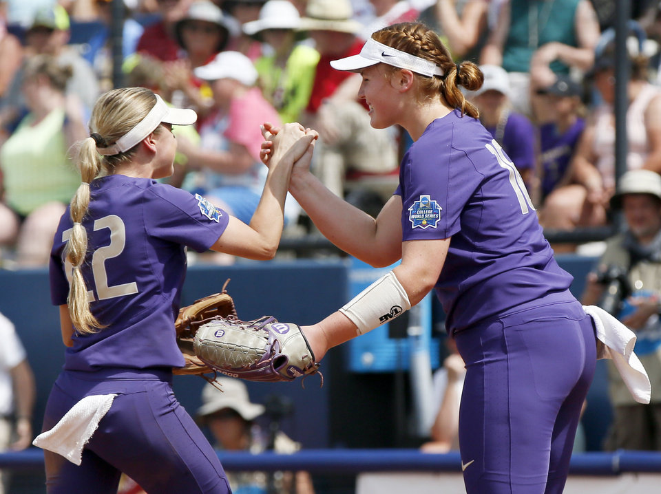 Photo - Washington's Sis Bates (22) and pitcher Gabbie Plain (16) celebrate at the end of the fifth inning during the second game of the Women's College World Series between the Oklahoma Sooners (OU) and Washington Huskies at USA Softball Hall of Fame Stadium in Oklahoma City, Thursday, May 31, 2018. Washington won 2-0. Photo by Nate Billings, The Oklahoman