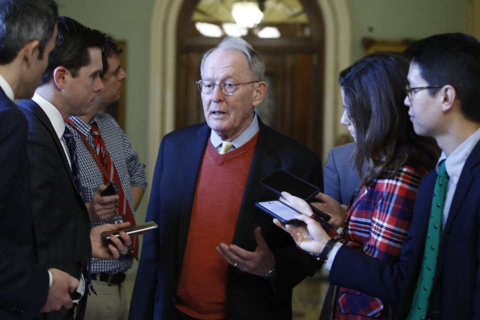Photo - Sen. Lamar Alexander, R-Tenn., talks to reporters as he walks past the Senate chamber prior to the start of the impeachment trial of President Donald Trump at the U.S. Capitol Friday Jan 31, 2020, in Washington. Senators continue the impeachment trial for President Donald Trump. (AP Photo/Steve Helber)