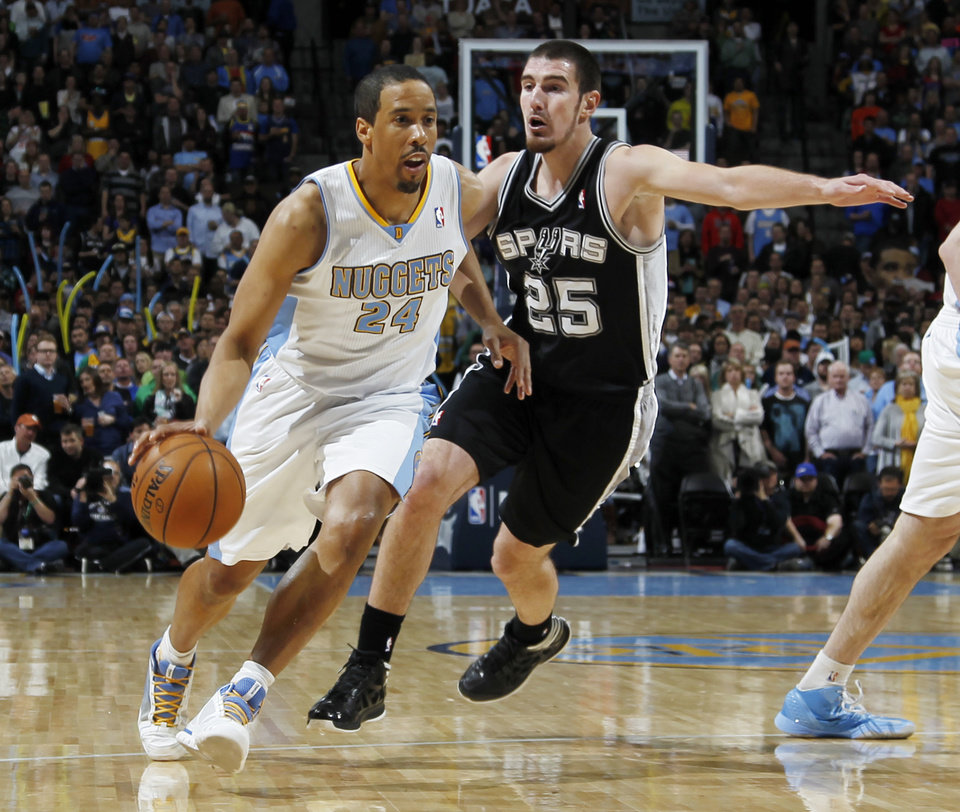 Photo - Denver Nuggets guard Andre Miller, left, drives past San Antonio Spurs guard Nando De Colo, of France, in the first quarter of an NBA basketball game in Denver, Wednesday, April 10, 2013. (AP Photo/David Zalubowski)