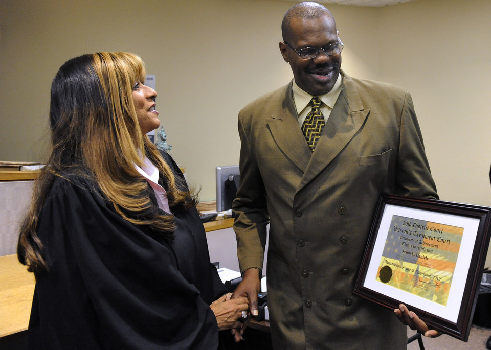 Photo - From left, Judge Leonia Lloyd, veteran Jason Daniels, graduating from veterans court at 36th District Court in Detroit on Thursday, Nov. 8, 2012. The court is a special court first created in Buffalo, N.Y. for drug-related and other non-violent offenses for military veterans. (AP Photo/The Detroit News, David Coates)