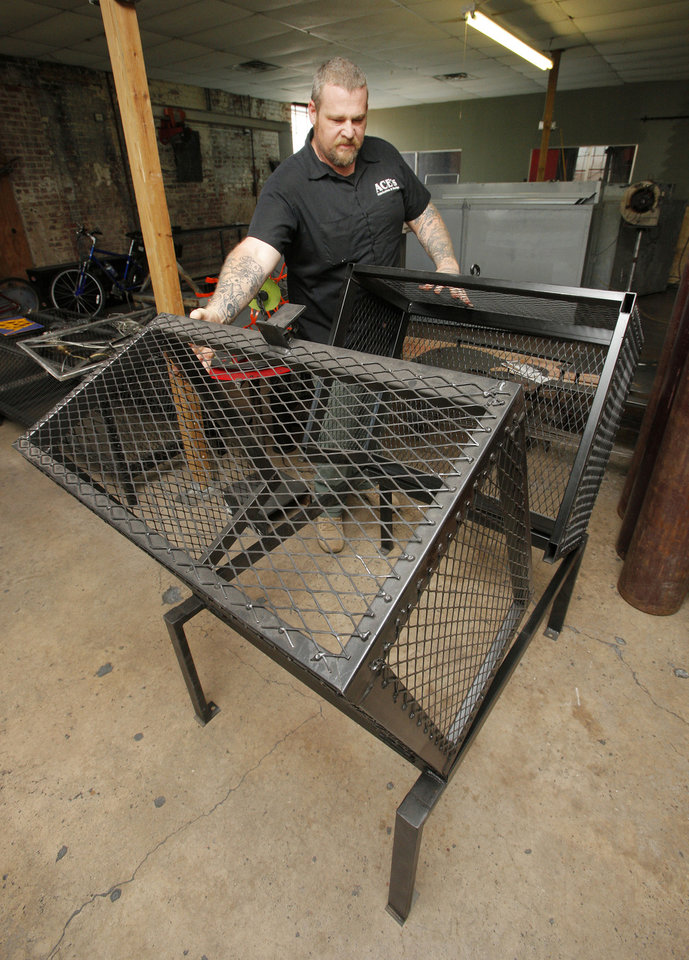Photo - Nathan White, owner of Ace's Fabrication and Design, with a finished Clamshell Cage on June 27. The cages are designed to protect air conditioning units from theft. Photo by Paul B. Southerland, The Oklahoman  PAUL B. SOUTHERLAND - PAUL B. SOUTHERLAND