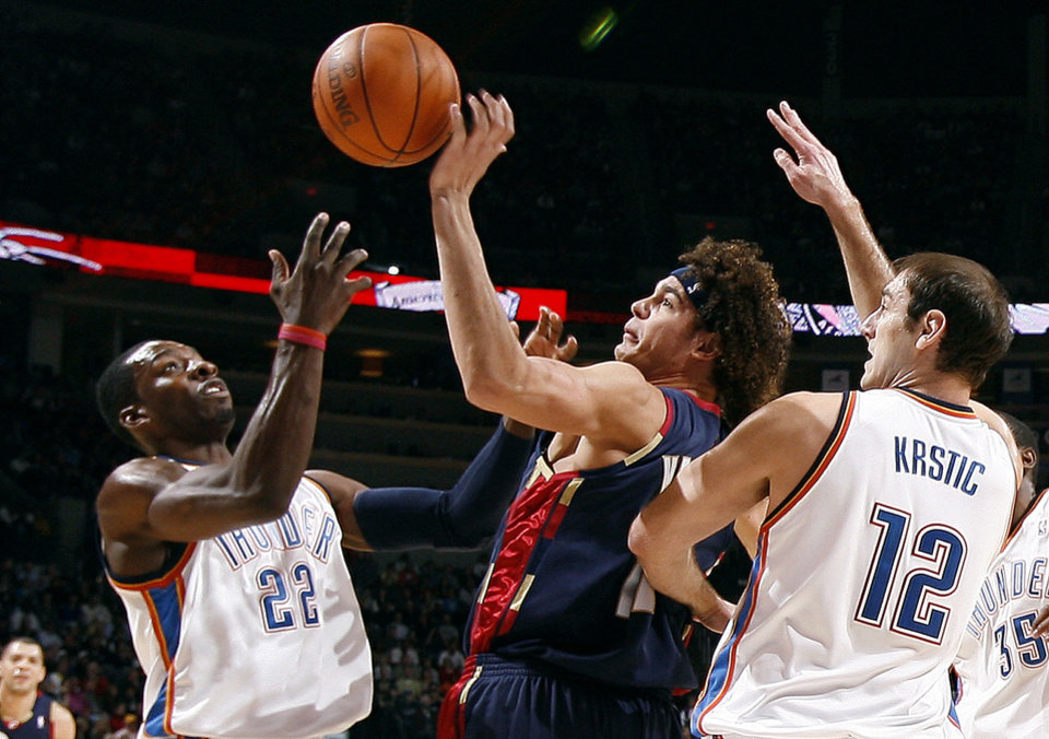 Photo - Oklahoma City's Jeff Green (22) and Nenad Krstic (12) fight Cleveland's Anderson Varejao (17) for a rebound during the NBA game between the Oklahoma City Thunder and the Cleveland Cavaliers, Sunday, Dec. 13, 2009, at the Ford Center in Oklahoma City. Photo by Sarah Phipps, The Oklahoman