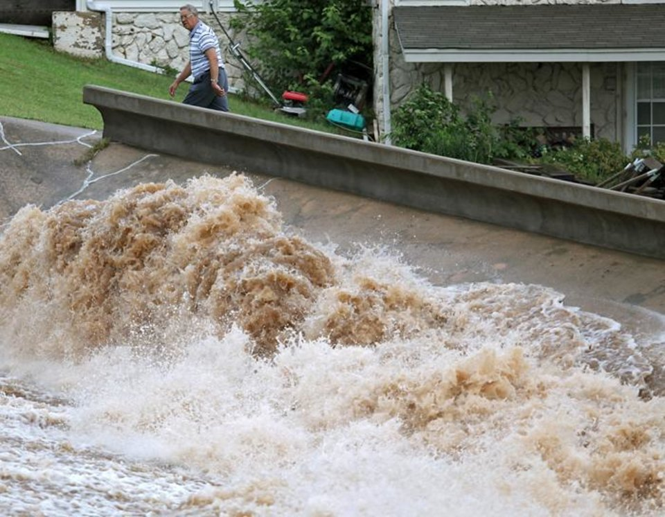 Photo -  RAIN / FLOOD / FLOODING: A local resident walks near flooding water as it spills over the dam south of Hefner between Macarthur and Rockwell in Oklahoma City on Monday, June 14, 2010. Photo by John Clanton, The Oklahoman ORG XMIT: KOD
