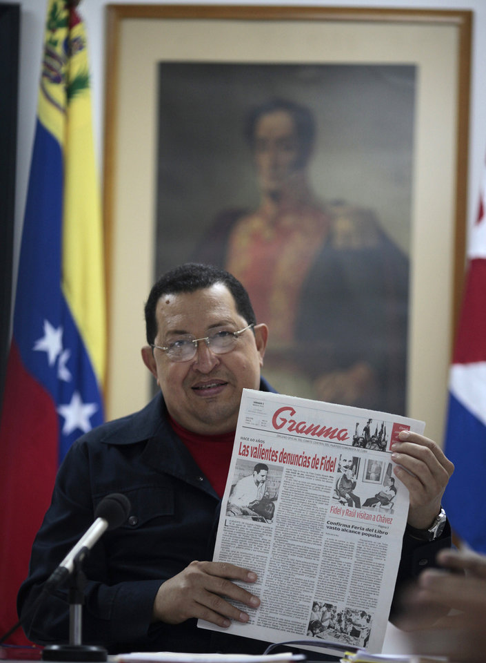 In this photo released by Miraflores Press Office Sunday March 4, 2012, Venezuela's President Hugo Chavez holds up a Saturday copy of Cuban newspaper, Granma during a televised speech at an undisclosed location in Havana, Cuba, Saturday March 3, 2012. Chavez appeared on television Sunday for the first time in nine days during which he underwent surgery in Cuba to remove a tumor. Chavez spoke firmly in footage recorded Saturday in Havana. (AP Photo/Miraflores Press Office/Marcelo Garcia)